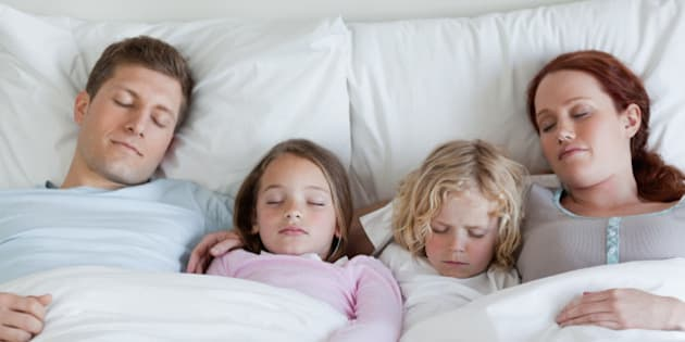 Adorable young family sleeping in the bed together