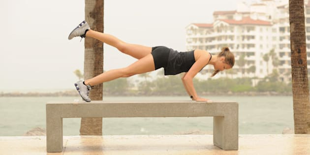Beautiful fitness model doing plank stretch on park bench near the beach.