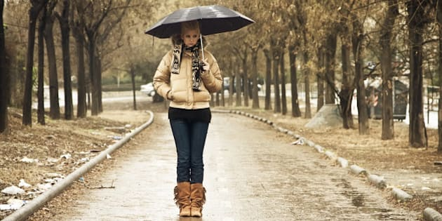 Young blond in walkway under rain
