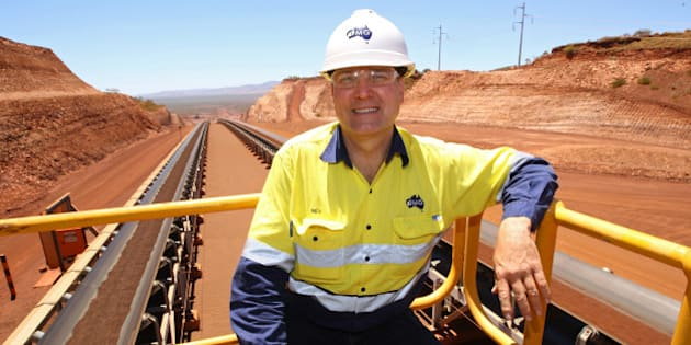 Neville 'Nev' Power, chief executive officer of Fortescue Metals Group Ltd., poses for a photograph in front of conveyors transporting iron ore during a tour of the company's Solomon mining hub in the Pilbara region, Western Australia, on Monday, Dec. 2, 2013. Fortescue, Australia's biggest issuer of junk-rated mining bonds, is targeting investment-grade status as strength in iron ore prices lets the company cut its debt burden. Photographer: Sergio Dionisio/Bloomberg via Getty Images