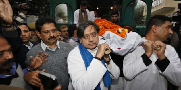 NEW DELHI, INDIA - JANUARY 18: Congress leader Shashi Tharoor (C) and relatives and friends carry the body of Tharoor's wife Sunanda Pushkar before her cremation at Lodhi Road crematorium, South Delhi, on January 18, 2014 in New Delhi, India. The wife of Indian Minister Shashi Tharoor, found dead in a luxury hotel after accusing her husband of being unfaithful, suffered an 'unnatural, sudden death', a doctor who performed an autopsy on her body said. Sunanda and Tharoor relation was disturbed as she was upset over reported text and tweet messages between her husband and Pakistani journalist Mehr Tarar. (Photograph by Raj k Raj/ Hindustan Times via Getty Images)