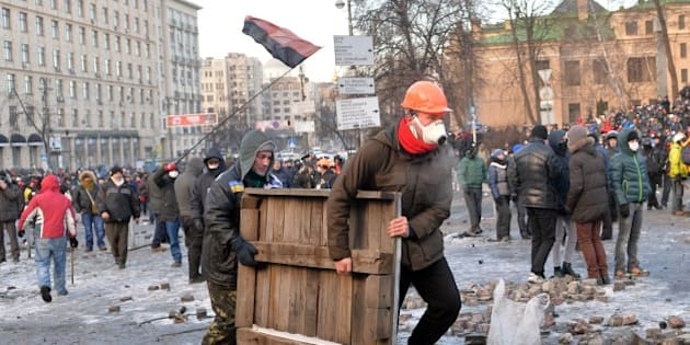Protesters carry a wooden board to build barricades during clashes with the police in Kiev on January 20, 2014. Radical opposition protesters Monday battled Ukrainian police in new clashes after bloody fighting the day earlier wounded over 200 people amid mounting fury over draconian new anti-protest laws. The clashes, the worst in Kiev in recent times, marked a spiralling of tensions after two months of demonstrations against President Viktor Yanukovych's refusal to sign a pact for closer integration with the EU. AFP PHOTO/ SERGEI SUPINSKY        (Photo credit should read SERGEI SUPINSKY/AFP/Getty Images)
