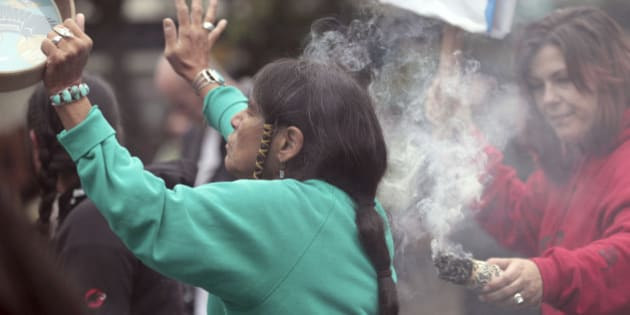 Ferntree, of Duncan, British Columbia, a member of the Cowichan Tribes, holds her hand up as she partakes in a smudging ceremony as smoke from a smoldering bundle of dried sweetgrass is directed toward her during a Native American protest against Columbus Day, Monday, Oct. 10, 2011, in Seattle. The fourth annual protest by the Oldgrowth Alliance included leaders and youth from Native American and Alaska Native communities speaking out against the annual holiday honoring Christopher Columbus' arrival in the Americas. Protest organizers say that Columbus could not have ?discovered? a western hemisphere already inhabited by about 100 million people. (AP Photo/Elaine Thompson)