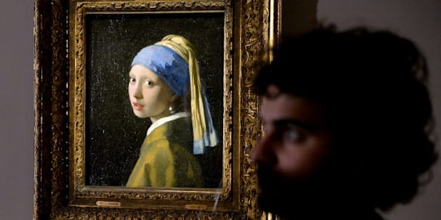 A woman stands next to the masterpiece 'Girl with a Pearl Earring' by Dutch painter Johannes Vermeer during a preview of the exhibition 'The Myth of the Golden Age, From Rembrandt to Vermeer' at Palazzo Fava in Bologna on January 30, 2014. The exhibition opens on February 8 and continues through May 25. AFP PHOTO/ VINCENZO PINTO        (Photo credit should read VINCENZO PINTO/AFP/Getty Images)