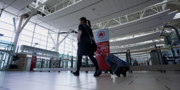 A flight attendant passes in front of the Air Canada check-in counters at Vancouver International Airport (YVR) in Richmond, British Columbia, Canada, on Wednesday, Nov. 13, 2013. The number of international visitors to Canada plunged 20 per cent since 2000 even as global travel soars, according to a sobering report being released Thursday by Deloitte Canada. Photographer: Ben Nelms/Bloomberg via Getty Images