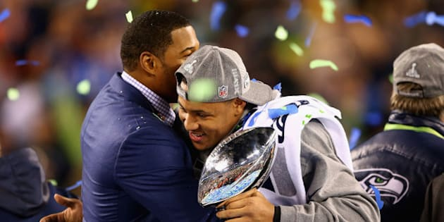 EAST RUTHERFORD, NJ - FEBRUARY 02:  Outside linebacker and Super Bowl MVP Malcolm Smith #53 of the Seattle Seahawks holds the Vince Lombardi Trophy and hugs Michael Strahan after winning Super Bowl XLVIII at MetLife Stadium on February 2, 2014 in East Rutherford, New Jersey.The Seahawks beat the Broncos 43-8.  (Photo by Elsa/Getty Images)
