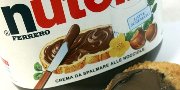 A knife spreads Fererro SpA's Nutella chocolate-hazelnut spread onto a piece of bread in Milan, Italy, on Thursday, Nov. 19, 2009. Michele Ferrero sold his first batch of Nutella spread in 1964. Four decades later, Italy's richest man must decide whether his company fast-tracks overseas growth by starting an auction for Cadbury Plc, or sticks to its recipe of homegrown sweets. Photographer: Giuseppe Aresu/Bloomberg via Getty Images