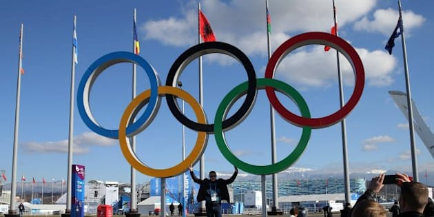 People pose with the Olympic rings inside Olympic Park at the Winter Olympics in Sochi, Russia, Thursday, Feb. 6, 2014. (Brian Cassella/Chicago Tribune/MCT via Getty Images)