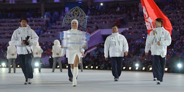 Hong Kong's flag bearer, speed skater Lui Pan-To Barton, leads his national delegation during the Opening Ceremony of the 2014 Sochi Winter Olympics at the Fisht Olympic Stadium on February 7, 2014 in Sochi. AFP PHOTO / ALBERTO PIZZOLI        (Photo credit should read ALBERTO PIZZOLI/AFP/Getty Images)