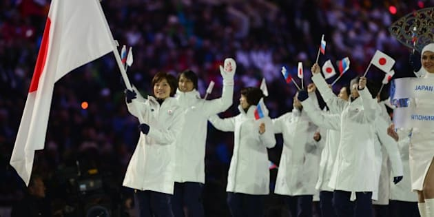 Japan's flag bearer, curler Ayumi Ogasawara, leads her national delegation during the Opening Ceremony of the 2014 Sochi Winter Olympics at the Fisht Olympic Stadium on February 7, 2014 in Sochi. AFP PHOTO / JOHN MACDOUGALL        (Photo credit should read JOHN MACDOUGALL/AFP/Getty Images)