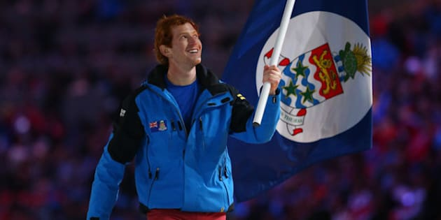 SOCHI, RUSSIA - FEBRUARY 07:  Skier Dow Travers of the Cayman Islands Olympic team carries his country's flag during the Opening Ceremony of the Sochi 2014 Winter Olympics at Fisht Olympic Stadium on February 7, 2014 in Sochi, Russia.  (Photo by Ryan Pierse/Getty Images)