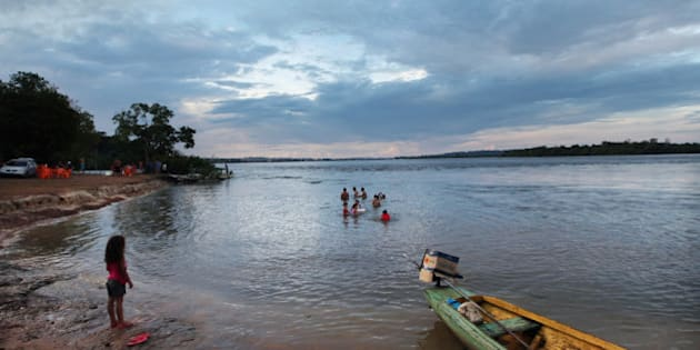 ALTAMIRA, BRAZIL - JUNE 16:   Brazilians bathe in the Xingu River near the area where the Belo Monte dam complex is under construction in the Amazon basin on June 16, 2012 in Altamira, Brazil. Belo Monte will be the world?s third-largest hydroelectric project and will displace up to 20,000 people while diverting the Xingu River and flooding as much as 230 square miles of rainforest.  The government says residents forced to relocate due to the dam will be compensated and that most will benefit from relocation. Opponents of the dam are skeptical of this claim. The controversial project is one of around 60 hydroelectric projects Brazil has planned in the Amazon to generate electricity for its rapidly expanding economy. While environmentalists and indigenous groups oppose the dam, many Brazilians support the project. The Brazilian Amazon, home to 60 percent of the world?s largest forest and 20 percent of the Earth?s oxygen, remains threatened by the rapid development of the country. The area is currently populated by over 20 million people and is challenged by deforestation, agriculture, mining, a governmental dam building spree, illegal land speculation including the occupation of forest reserves and indigenous land and other issues. Over 100 heads of state and tens of thousands of participants and protesters will descend on Rio de Janeiro, Brazil, later this month for the Rio+20 United Nations Conference on Sustainable Development or ?Earth Summit?. Host Brazil is caught up in its own dilemma between accelerated growth and environmental preservation.  (Photo by Mario Tama/Getty Images)