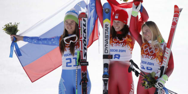 Women's downhill gold medal winners Slovenia's Tina Maze, left, and Switzerland's Dominique Gisin, center, and bronze medal winner, Switzerland's Lara Gut, stand on the podium during a flower ceremony at the Sochi 2014 Winter Olympics, Wednesday, Feb. 12, 2014, in Krasnaya Polyana, Russia. (AP Photo/Christophe Ena)