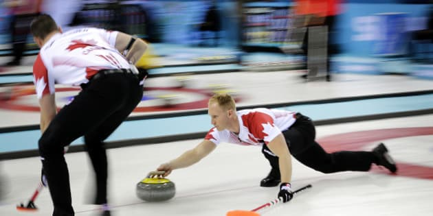 Canada's skip Brad Jacobs, right, delivers the rock while his teammate Ryan Harnden, Left, prepares to sweep the ice during the men's curling competition against Germany at the 2014 Winter Olympics, Monday, Feb. 10, 2014, in Sochi, Russia. (AP Photo/Wong Maye-E)