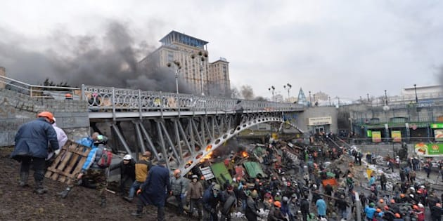 Anti-government protesters reinforce a barricade during clashes with the police in the center of Kiev on February 20, 2014. Armed protesters stormed police barricades in Kiev on Thursday in renewed violence that killed at least 26 people and shattered an hours-old truce as EU envoys held crisis talks with Ukraine's embattled president. Bodies of anti-government demonstrators lay amid smouldering debris after masked protesters hurling Molotov cocktails and stones forced police from Kiev's iconic Independence Square -- the epicentre of the ex-Soviet country's three-month-old crisis. AFP PHOTO/ SERGEI SUPINSKY        (Photo credit should read SERGEI SUPINSKY/AFP/Getty Images)