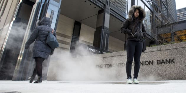 TORONTO, ON - JANUARY 20  - Jessica Bathan stands on a vent releasing warm air on Bay Street south of King Street West while waiting for a bus during a cold weather alert in Toronto on January 20, 2014.        (Carlos Osorio/Toronto Star via Getty Images)