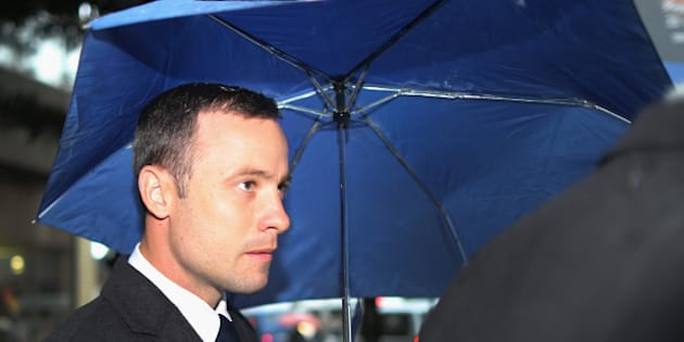 PRETORIA, SOUTH AFRICA - MARCH 04:  Oscar Pistorius shelters from the rain as he makes his way to North Gauteng High Court for the second day of his trial accused of the murder of his girlfriend Reeva Steenkamp on March 4, 2014 in Pretoria, South Africa. Olympic and Paralympic athlete Oscar Pistorius, aged 27, is accused of murdering his girlfriend Reeva Steenkamp. Pistorius denies the allegation claiming he mistook Steenkamp for an intruder inside their home on Valentines Day 2013.  (Photo by Christopher Furlong/Getty Images)