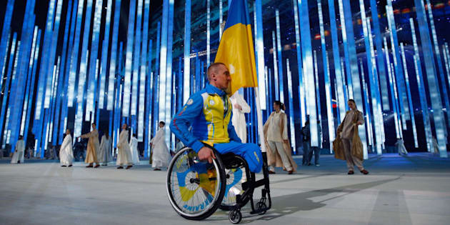 SOCHI, RUSSIA - MARCH 07:  Flag bearer Mykailo Tkachenko of the Ukraine enters the arena during the Opening Ceremony of the Sochi 2014 Paralympic Winter Games at Fisht Olympic Stadium on March 7, 2014 in Sochi, Russia. The rest of the Ukraine team refused to enter the arena as a protest against the present political tension between Ukraine and Russia.  (Photo by Tom Pennington/Getty Images)
