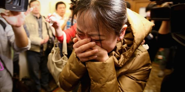 BEIJING, CHINA - MARCH 09: A relative of a passenger onboard Malaysia Airlines flight MH370 cries out at a local hotel where families are gathered on March 9, 2014 in Beijing, China. Malaysia Airline Flight MH370 from Kuala Lumpur to Beijing and carrying 239 onboard was reported missing after the crew failed to check in as scheduled while flying over the sea between Malaysia and Ho Chi Minh City in Vietnam, according to published reports.  (Photo by Feng Li/Getty Images)