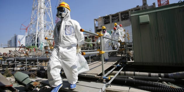 Members of the media and Tokyo Electric Power Co. (Tepco) employees, wearing protective suits and masks, walk towards the common spent fuel facility during a visit to the company's Fukushima Dai-Ichi nuclear power plant in Okuma, Fukushima Prefecture, Japan, on Wednesday, March 6, 2013. Tepco's Fukushima Dai-Ichi plant had three reactor core meltdowns after it was hit by an earthquake and tsunami on March 11, 2011. Photographer: Issei Kato/Pool via Bloomberg