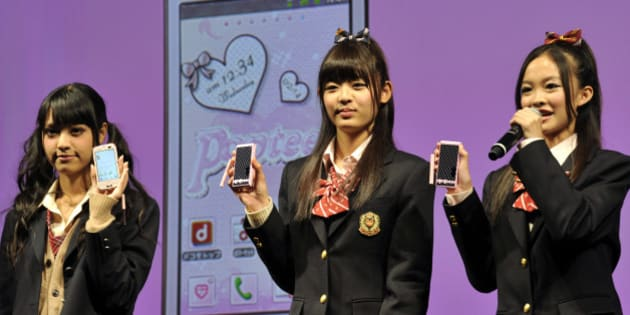 Models display Japanese mobile communication provider NTT DoCoMo's smartphones targeting teenaged girls, produced by Japanese electronics giant Fujitsu, at a press conference in Tokyo on October 18, 2011. NTT DoCoMo unveiled four models of smartphones for the LTE next-generation high-speed communication network system.  AFP PHOTO / Yoshikazu TSUNO (Photo credit should read YOSHIKAZU TSUNO/AFP/Getty Images)