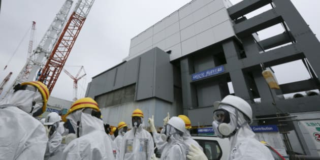 Members of the media and Tokyo Electric Power Co. (Tepco) employees wearing protective suits and masks stand in front of the building housing the No. 4 reactor at the Fukushima Dai-ichi nuclear power plant in Okuma, Fukushima Prefecture, Japan, on Thursday, Nov. 7, 2013. Tepco, which returned to profitability in its first-half earnings report on Oct. 31, is handling an estimated 11 trillion yen ($112 billion) cleanup of the nuclear plant wrecked by an earthquake and tsunami in 2011. Photographer: Kimimasa Mayama/Pool via Bloomberg