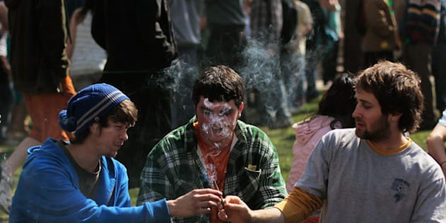 BOULDER, CO - APRIL 20:  Young men smoke a marijuana cigarette during a 'smoke out' with thousands of others April 20, 2010 at the University of Colorado in Boulder, Colorado. April 20th has become a de facto holiday for marijuana advocates, with large gatherings and 'smoke outs' in many parts of the United States.  Colorado, one of 14 states to allow use of medical marijuana, has experienced an explosion in marijuana dispensaries, trade shows and related businesses in the last year as marijuana use becomes more mainstream here.  (Photo by Chris Hondros/Getty Images)