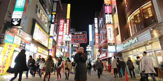 An employee holds a sign for a 'okonomiyaki' restaurant at night in the Shibuya district of Tokyo, Japan, on Sunday, Feb. 16, 2014. Japans economy grew at a pace slower than any economist surveyed by Bloomberg News forecast in the fourth quarter, underscoring risks to the recovery as a sales-tax increase looms in April. Photographer: Yuriko Nakao/Bloomberg via Getty Images