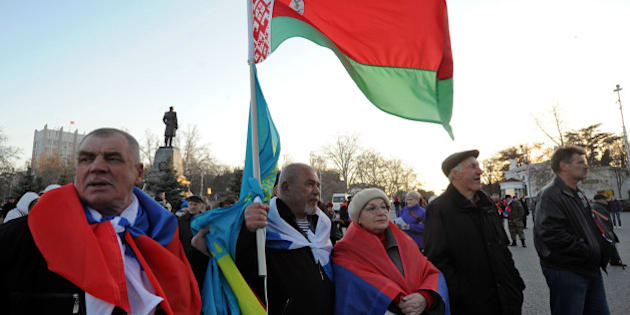 Pro-Russian activists hold (From L) the flags of Russia, Kazakhstan and Belarus during a gathering in Sevastopol on March 15, 2014. Crimea's referendum on March 16, 2014  to break from Ukraine and join Russia is regarded as illegitimate by the West but seen in Moscow as an example of self-determination like Kosovo leaving Serbia. The referendum comes in direct response to three months of deadly protests that on February 22 toppled the pro-Kremlin president and brought to power a new European-leaning team in Kiev that threatens to shatter President Vladimir Putin's dream of rebuilding a post-Soviet empire. AFP PHOTO/ VIKTOR DRACHEV        (Photo credit should read VIKTOR DRACHEV/AFP/Getty Images)