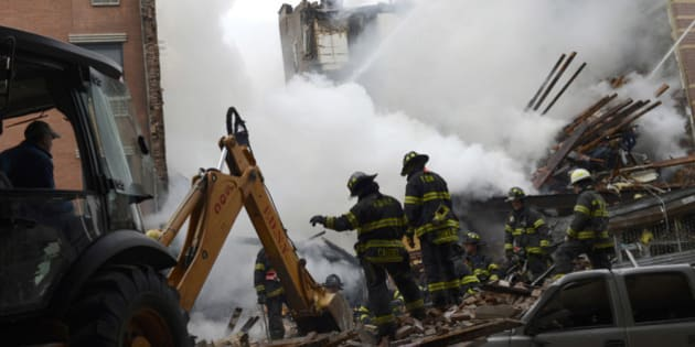 NEW YORK, NY - MARCH 12:  In this image handout provided by the Office of Mayor of New York, firefighters from the Fire Department of New York (FDNY) use an excavator to remove rubble as they respond to a five-alarm fire and building collapse at 1646 Park Ave in the Harlem neighborhood of Manhattan March 12, 2014 in New York City. Reports of an explosion were heard before the collapse of two multiple-dwelling buildings at East 116th St. and Park Avenue that left at least 17 injured and a number of people are missing.  (Photo by Rob Bennett/Office of Mayor of New York/Getty Images)