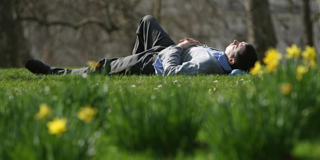 A man lies in the sun in St James's Park, London, as Londoners enjoy the warm weather.