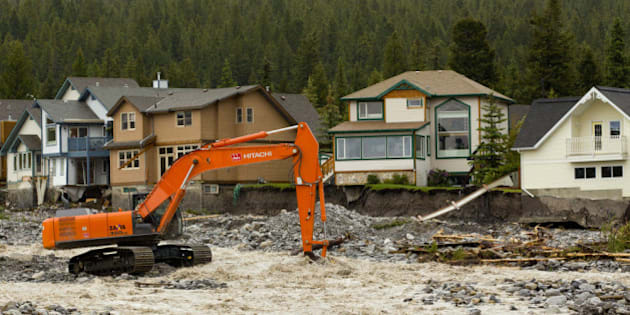 CANMORE, CANADA - JUNE 21:  A man operating an excavator works to shore up the flooding Cougar Creek on June 21, 2013 in Canmore, Alberta, Canada. Widespread flooding caused by torrential rains washed out bridges and roads, prompting the evacuation of thousands.  (Photo by John Gibson/Getty Images)