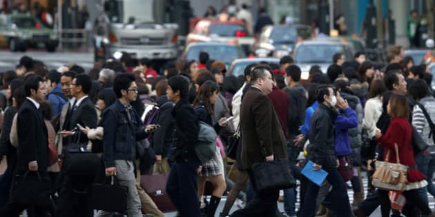 Pedestrians cross an intersection in the Shibuya district of Tokyo, Japan, on Friday, Nov. 22, 2013. Monthly capital inflows into Japanese real estate investment trusts rose to the highest since March 2010 in September amid expectations that the 2020 Olympic Games in Tokyo will help boost the property market and on signs commercial land prices in major cities are rebounding, according to a report by the Association of Real Estate Securitization. Photographer: Kiyoshi Ota/Bloomberg via Getty Images