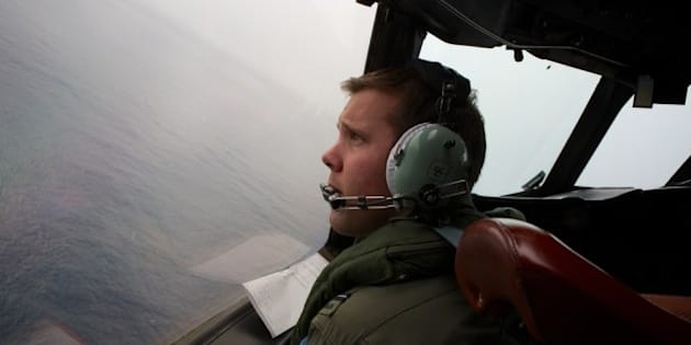 IN FLIGHT - MARCH 24:  Co-Pilot, Flying Officer Marc Smith looks out as he turns his RAAF AP-3C Orion aircraft at low level in bad weather while searching for missing Malaysia Airways Flight MH370 on March 24, 2014 off the South West Coast of Perth, Australia. Malaysian Prime Minister Najib Razak spoke at a press conference today to announce that fresh analysis of available satellite data has concluded that missing flight MH370's final position was in the southern Indian Ocean. French authorities reported a satellite sighting of objects in an area of the southern Indian Ocean where China and Australia have also reported similar sightings of potential debris from the flight that went missing on March 8. (Photo by Richard Wainwright - Pool/Getty Images)