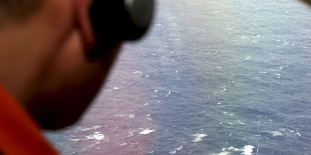 Kazuhiko Morisawa looks out of a window of a Japan Coast Guard Gulfstream aircraft during the search for wreckage and debris of missing Malaysia Airlines Flight MH370 in the Southern Indian Ocean on April 1, 2014. Malaysia revealed the full radio communications with the pilots of its missing flight on April 1, but the routine exchanges shed no light on the mystery as an Indian Ocean search for wreckage bore on with no end in sight.   AFP PHOTO / POOL / Rob GRIFFITH        (Photo credit should read ROB GRIFFITH/AFP/Getty Images)