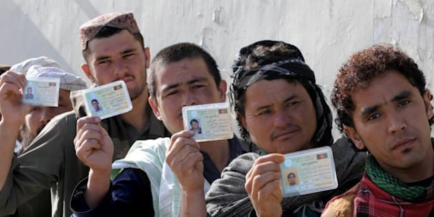 Afghan voters display their national identity cards as they queue to cast their votes at a local polling station in Kandahar on April 5, 2014. Afghan voters went to the polls to choose a successor to President Hamid Karzai, braving Taliban threats in a landmark election held as US-led forces wind down their long intervention in the country. AFP PHOTO/Banaras KHAN        (Photo credit should read BANARAS KHAN/AFP/Getty Images)