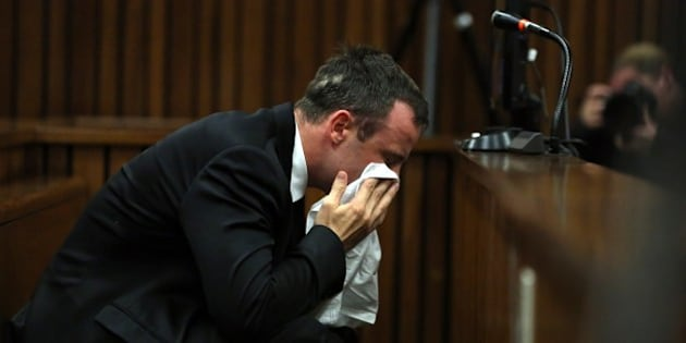 South African Paralympic track star Oscar Pistorius wipes his face during his trial in Court in Pretoria on April 7, 2014. As the defence opens its case, the 27-year-old Paralympian will give the court his first account of why he shot dead his model girlfriend Reeva Steenkamp in the early hours of Valentine's Day in 2013.    POOL AFP PHOTO Themba Hadebe        (Photo credit should read THEMBA HADEBE/AFP/Getty Images)