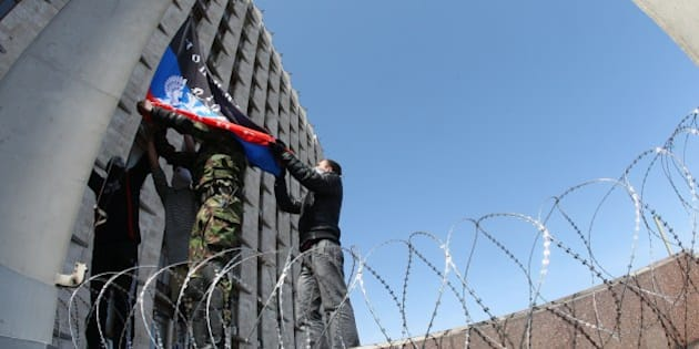 Pro-Russian activists who seized the main administration building in the eastern Ukrainian city of Donetsk rise up a flag of the so-called Republic of Donetsk on April 7, 2014, in Donetsk. They proclaimed on April 7 the creation of a sovereign 'people's republic' independent of Kiev's rule. Ukraine's embattled Prime Minister on April 7 accused Russia of trying to 'dismember' his country by plotting seizures of government buildings in eastern regions that are seeking to break away from Kiev. AFP PHOTO/ ALEXANDER KHUDOTEPLY        (Photo credit should read Alexander KHUDOTEPLY/AFP/Getty Images)
