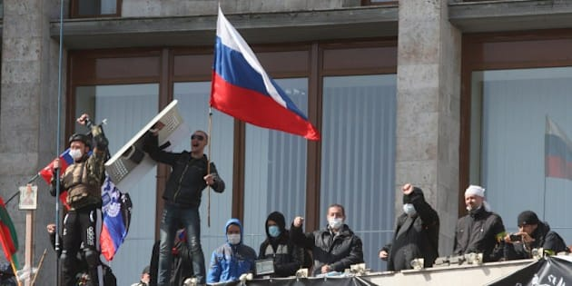 Pro-Russian activists who seized the main administration building in the eastern Ukrainian city of Donetsk deploy a flag of the so-called Donetsk Republic and hold a Russian flag on April 7, 2014, in Donetsk. They proclaimed on April 7 the creation of a sovereign 'people's republic' independent of Kiev's rule. Ukraine's embattled Prime Minister on April 7 accused Russia of trying to 'dismember' his country by plotting seizures of government buildings in eastern regions that are seeking to break away from Kiev. AFP PHOTO/ ALEXANDER KHUDOTEPLY        (Photo credit should read Alexander KHUDOTEPLY/AFP/Getty Images)