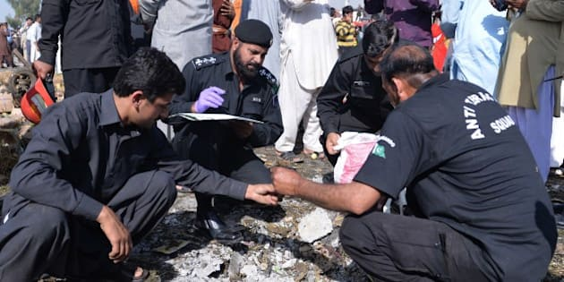 Pakistani security officials collect evidence at the site of a bomb explosion in a fruit and vegetable market in Islamabad on April 9, 2014. A bomb explosion killed at least 22 people and wounded 50 others in Islamabad's bustling fruit and vegetable market, police and hospital officials said. AFP PHOTO/Aamir QURESHI        (Photo credit should read AAMIR QURESHI/AFP/Getty Images)