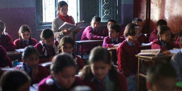 In a picture taken on November 21, 2012, Drishti Silwal (back row L), a 12 year old Brahmin Nepali girl reads a book at school in Kathmandu. Dristhi returned to school after spending 7 days staying in the darkness of her bedroom as part of an isolation ritual during her first menstruation. Usually Brahmans stay isolated for 21 days in the dark, without the permission to look outside, see any men, pray or cook, but in modern families the ritual can be reduced to 7 days and Drishti was allowed to read. AFP PHOTO / MATTHIEU ALEXANDRE        (Photo credit should read MATTHIEU ALEXANDRE/AFP/Getty Images)