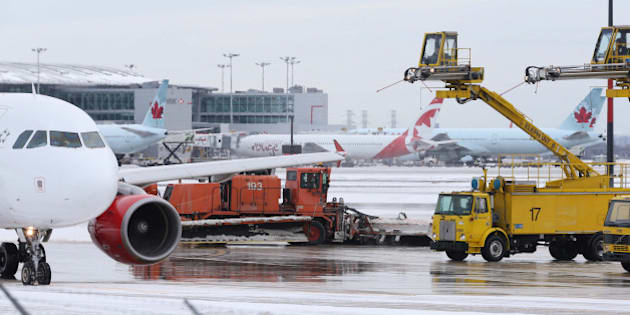 TORONTO, ON - JANUARY 20: Air Canada planes get de-iced on the tarmac by crews at Pearson International Airport in Toronto. Toronto is back under a cold weather alert, causing yet more flight delays and travel havoc. January 20, 2014.        (Rene Johnston/Toronto Star via Getty Images)