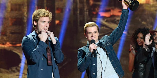 LOS ANGELES, CA - APRIL 13:  Actors Sam Claflin (L) and Josh Hutcherson accept the Movie of the Year award for 'The Hunger Games: Catching Fire' onstage at the 2014 MTV Movie Awards at Nokia Theatre L.A. Live on April 13, 2014 in Los Angeles, California.  (Photo by Kevin Mazur/WireImage)