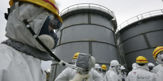 A Tokyo Electric Power Co. (Tepco) employee, left, wearing a protective suit and mask measures radiation as members of the media also in protective suits and masks stand in front of storage tanks for radioactive water at the Fukushima Dai-ichi nuclear power plant in Okuma, Fukushima Prefecture, Japan, on Thursday, Nov. 7, 2013. Tepco, which returned to profitability in its first-half earnings report on Oct. 31, is handling an estimated 11 trillion yen ($112 billion) cleanup of the nuclear plant wrecked by an earthquake and tsunami in 2011. Photographer: Kimimasa Mayama/Pool via Bloomberg