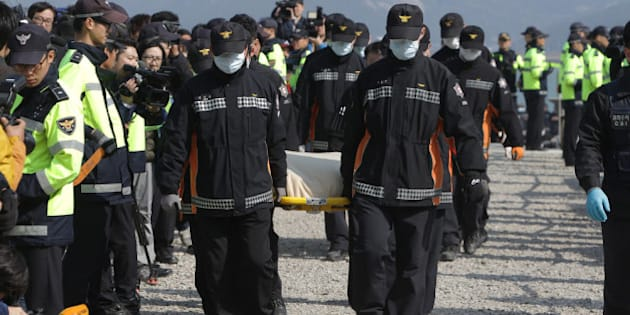JINDO-GUN, SOUTH KOREA - APRIL 21:  Rescue workers carry a victim of the sunken ferry off the coast of Jindo Island on April 21, 2014 in Jindo-gun, South Korea. At least sixty four people are reported dead, with 238 still missing. The ferry identified as the Sewol was carrying about 470 passengers, including the students and teachers, traveling to Jeju Island.  (Photo by Chung Sung-Jun/Getty Images)