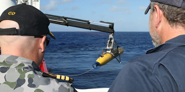 AT SEA - APRIL 17:  In this handout image provided by Commonwealth of Australia, Department of Defence, Commander James Lybrand Mission Commander ADV Ocean Shield (L)and Chris 'Sharkie' Moore, Phoenix Team Lead, watch the launching the Phoenix Autonomous Underwater Vehicle (AUV) Artemis off the deck of ADV Ocean Shield on April 17, 2014. Twenty-six nations have been involved in the search for Malaysia Airlines Flight MH370 since it disappeared more than a month ago.  The Malaysian Airways aircraft went missing on 8th March 2014 whilst on a flight between Kuala Lumpur and Beijing. (Photo by LSIS Bradley Darvill/Australia Department of Defence via Getty Images)