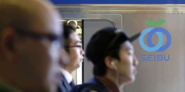 Passengers walk past the Seibu Railway Co. logo displayed on a train at a train station in Tokyo, Japan, on Monday, April 7, 2014. Seibu Holdings Inc. is targeting a price of 2,300 yen a share for an initial public offering by investors including Cerberus Capital Management LP, according to two people familiar with the matter. Photographer: Kiyoshi Ota/Bloomberg via Getty Images