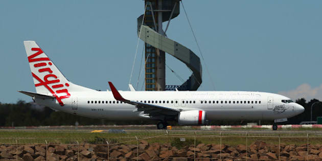 A Boeing Co. 737 aircraft operated by Virgin Australia Holdings Ltd. taxis on the runway at Sydney Airport in Sydney, Australia, on Friday, Dec. 6, 2013. Qantas Airways Ltd.'s credit rating was cut to junk at Standard & Poor's a day after the carrier flagged a record first-half loss and 1,000 job cuts. Photographer: Brendon Thorne/Bloomberg via Getty Images