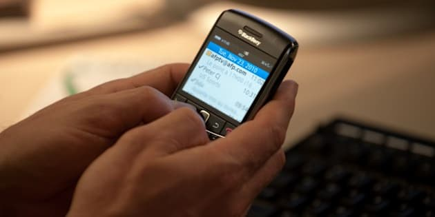 A man looks at his email on a Blackberry in Washington on November 23, 2010. Americans will take a break from the office over the Thanksgiving and Christmas holidays but most won't stop checking their work emails, according to a survey released on Tuesday. The Harris Interactive survey conducted for Xobni, an email software firm, found that 59 percent of employed American adults will consult work emails over the holidays. Fifty-five percent will check work emails at least once a day and 28 percent will do so multiple times throughout the day, the survey found.  AFP PHOTO/Nicholas KAMM (Photo credit should read NICHOLAS KAMM/AFP/Getty Images)