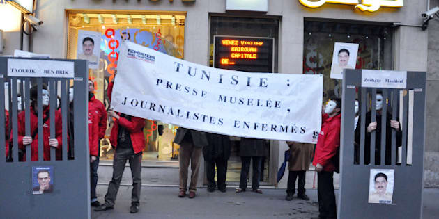 Members of Reporters without Borders (RSF) hold a banner reading 'Tunisia: muzzled press, prisoned journalists' as they protest to call for the release of Hedi Zoghlami (R) and Tunisian journalist Taoufik Ben Brik on November 18, 2009 in Paris. Ben Brik, 41, was arrested after an alleged altercation with a woman and charged with violating public decency, defamation, assault and damaging private property. His is currently being held at Mornaguia prison, 20km north of Tunis and his trial is scheduled to begin on November 19th. AFP PHOTO ARTHUR HERBULOT (Photo credit should read ARTHUR HERBULOT/AFP/Getty Images)